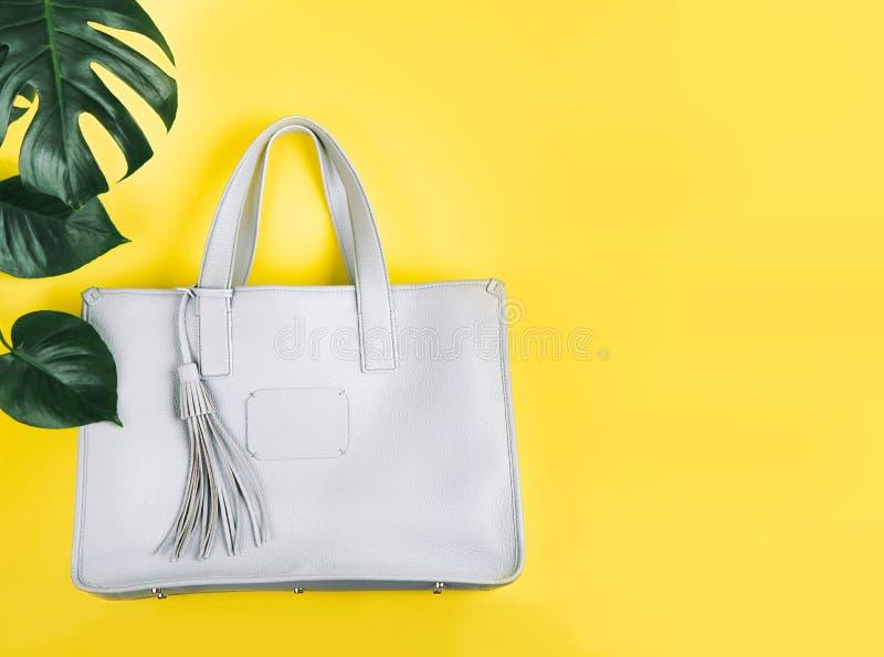 Weibliche Handtasche und gr?nes Blatt stockfoto