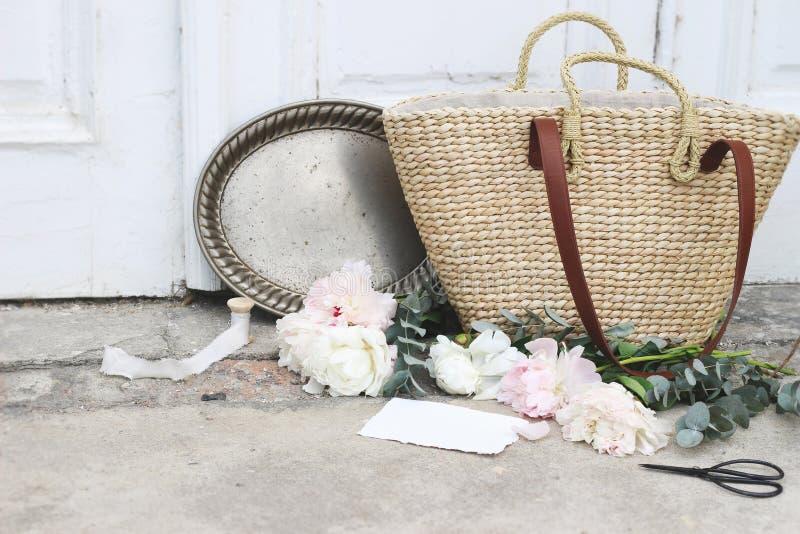 Weibliche Heiratsstilllebenzusammensetzung mit französischer Korbtasche des Strohs, rosa Pfingstrosenblumen, Eukalyptus, Weinlese stockfoto