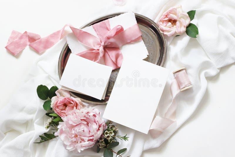 Weibliche Hochzeit, Geburtstagsmodellszene Grußkarten des leeren Papiers, Umschlag, Eukalyptus, rosa Rosen, Pfingstrosenblumen stockbilder