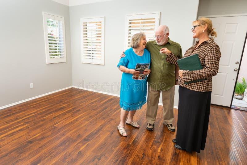 Weibliche Immobilienagentur Handing New House befestigt zum älteren Erwachsenen lizenzfreies stockbild