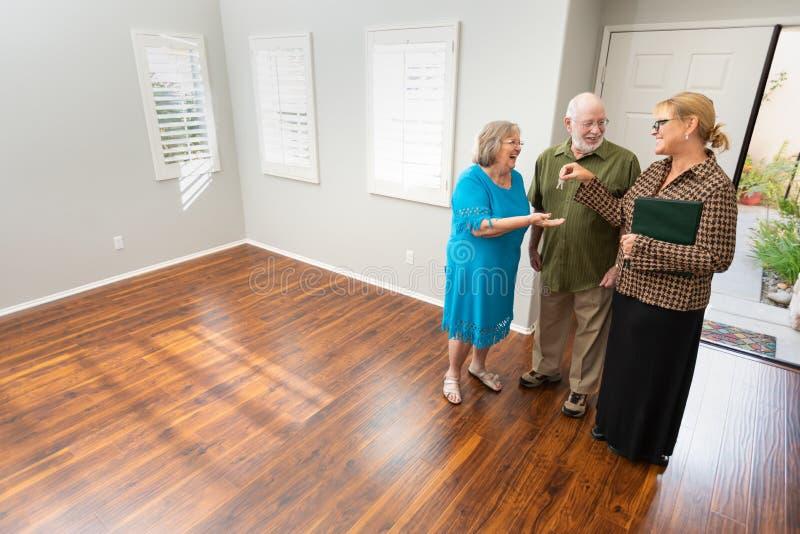Weibliche Immobilienagentur Handing New House befestigt zum älteren Erwachsenen lizenzfreie stockfotos