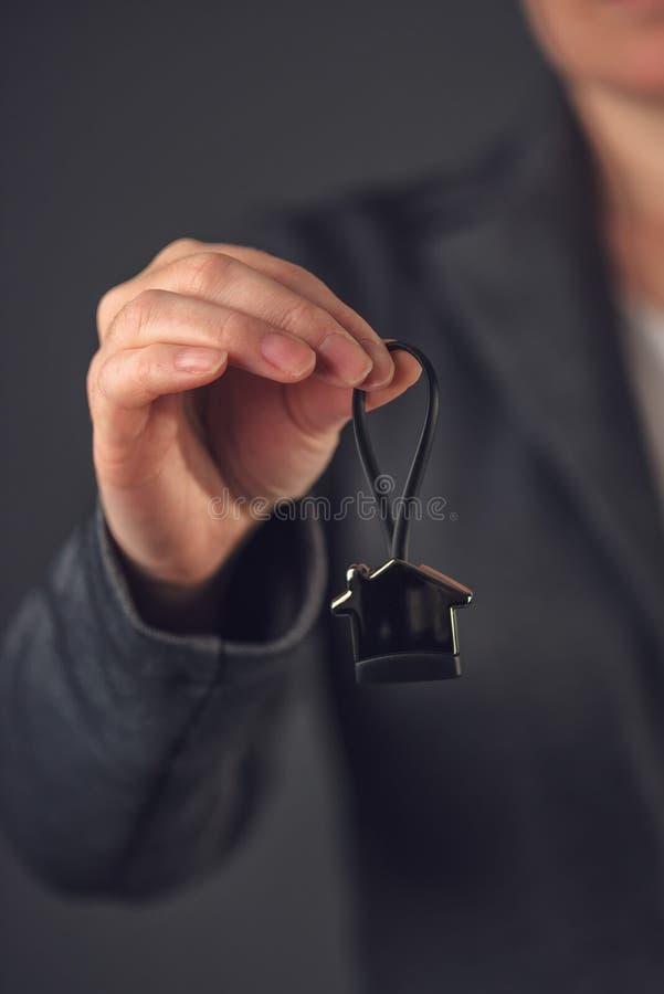 Weibliche Immobilienagentur mit Hausmodell-Schlüsselring lizenzfreie stockfotografie