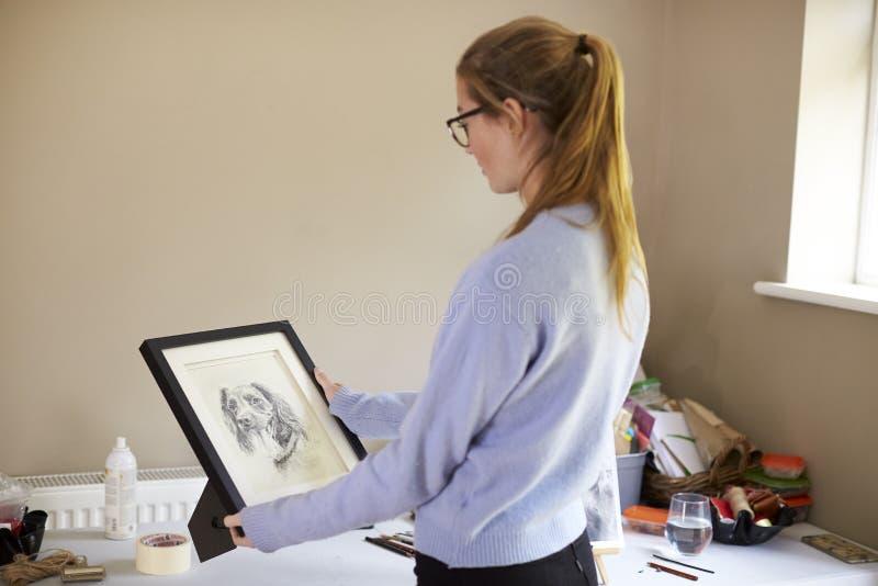 Weibliche Jugendkünstler-Holding Framed Charcoal-Zeichnung des Hundes im Studio lizenzfreie stockbilder