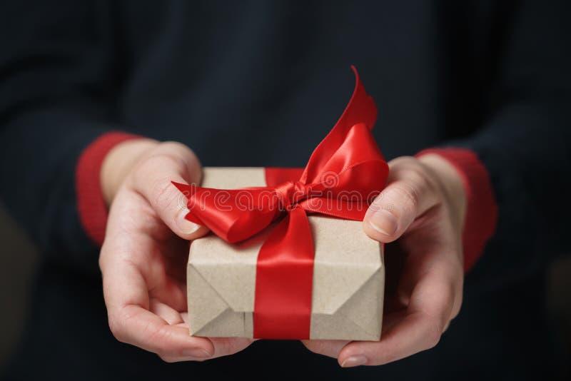 Weibliche jugendlich Hände zeigen Kraftpapiergeschenkbox mit rotem Bogen lizenzfreie stockbilder
