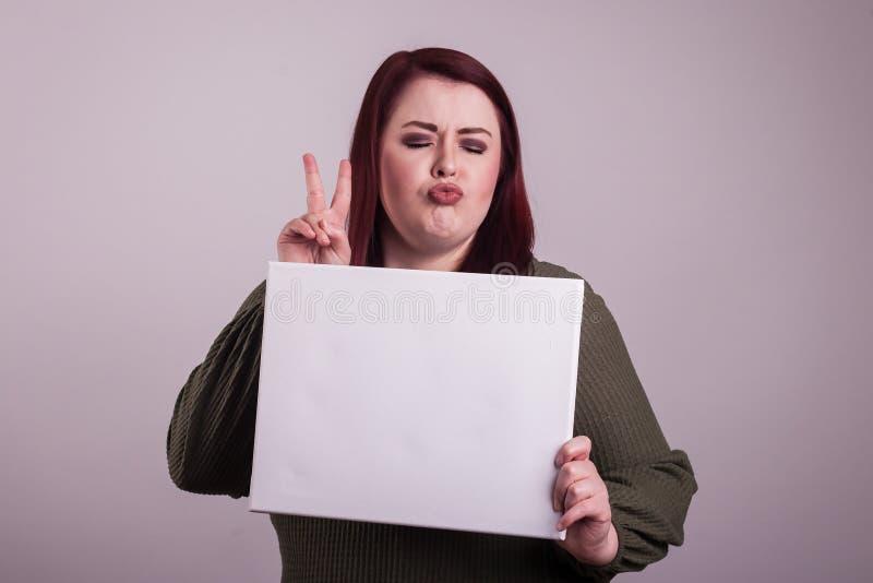 Weibliche junge Frau, welche die verziehenden Lippen eines leeren weißen Zeichens geben ein Friedenszeichen hält stockfotos