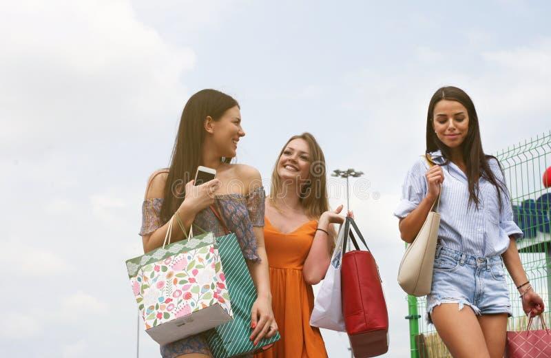 Weibliche junge Freunde, die das Einkaufen in der Stadt tun lizenzfreie stockbilder