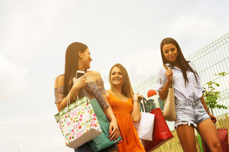 Weibliche junge Freunde, die das Einkaufen in der Stadt tun stockfotos