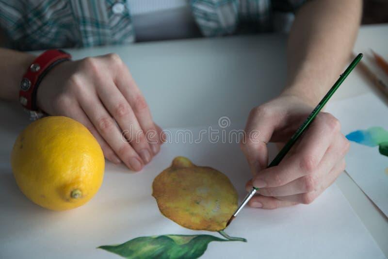 Weibliche Künstler ` s Hand auf dem Tisch lizenzfreie stockbilder