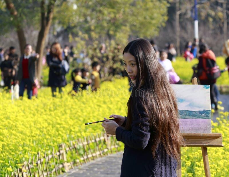 Weibliche Künstlermalerei im Rapsfeld lizenzfreies stockbild