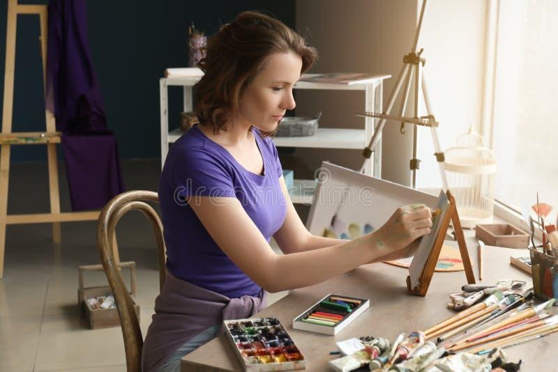 Weibliche Künstlerzeichnung mit Kreiden in der Werkstatt lizenzfreie stockfotos