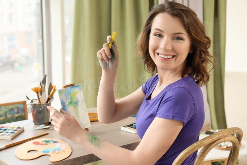 Weibliche Künstlerzeichnung mit Kreiden in der Werkstatt stockfotos
