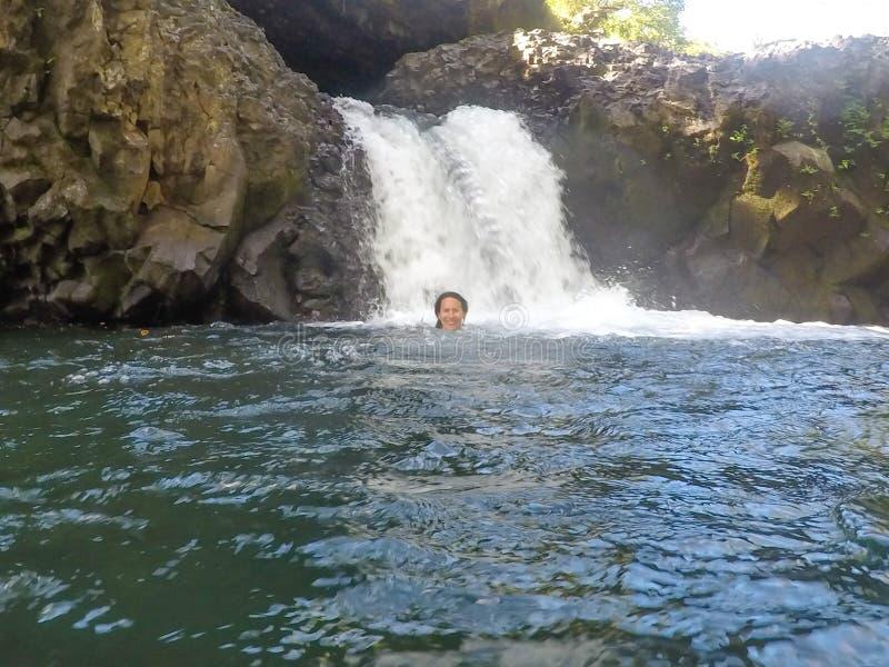 Weibliche kaukasische touristische Schwimmen im Wasser bei Togitogiga Waterfa lizenzfreie stockfotografie