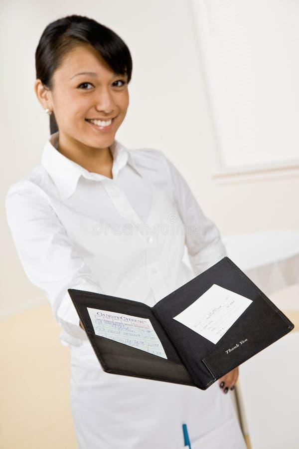Weibliche Kellnerin bietet Rechnung an lizenzfreies stockbild