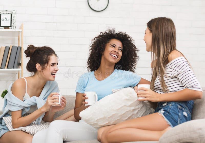 Weibliche klatschende und lachende Zimmergenossen, trinkender Kaffee stockfotos