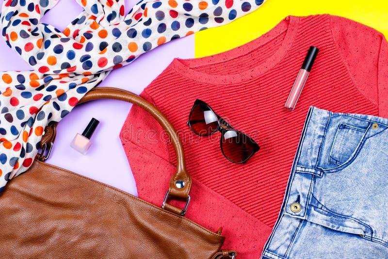 Weibliche Kleidung des Herbstes - rote Strickjacke, Blue Jeans, Lederhandtasche, druckte Schal, Zubehör und bildet Produkte stockbild