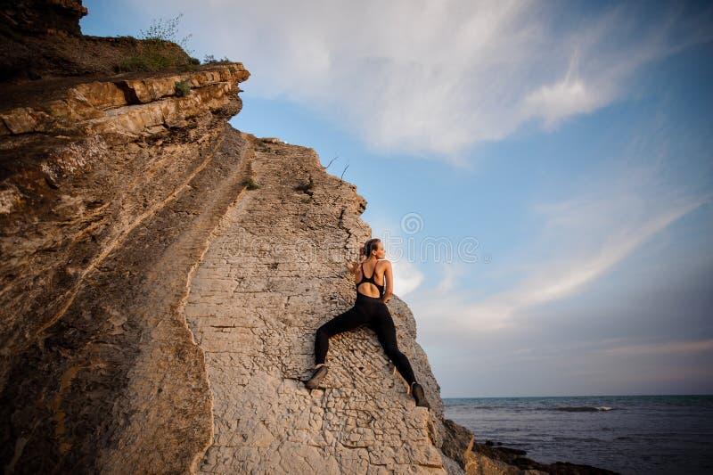 Weibliche Klettereraufstiege auf felsiger Wand stockfoto
