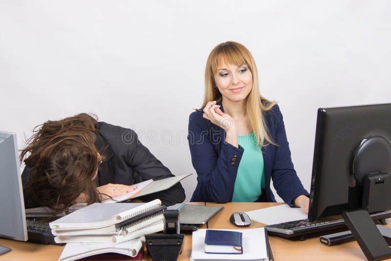 Weibliche Kollegen im Büro, man waren auf einen Stapel von Ordnern, der andere eingeschlafen, der glücklich den Bildschirm betrac stockbild