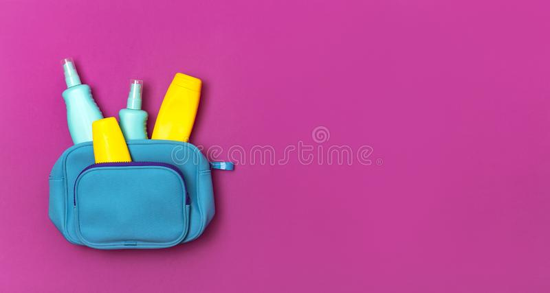Weibliche Kosmetik bauschen sich, kosmetische Produkte, gelbe Lichtschutzflasche und sunblock Lotion, Spray auf die helle rosa pi lizenzfreies stockfoto
