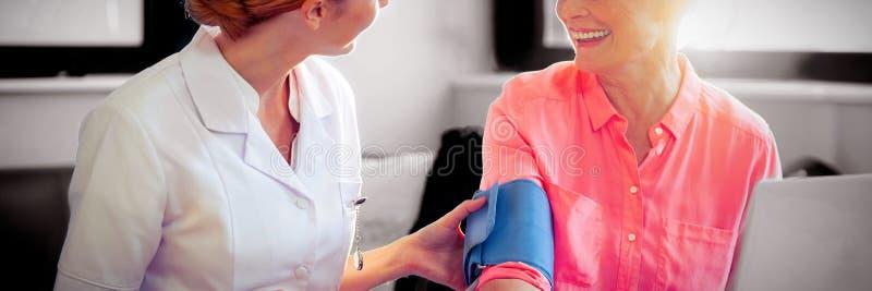 Weibliche Krankenschwester, die Blutdruck der älteren Frau überprüft stockfotografie