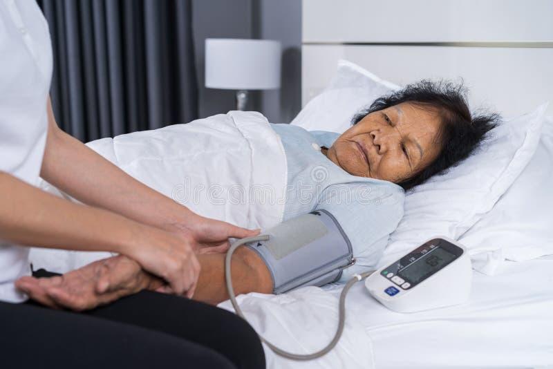 Weibliche Krankenschwester, die Blutdruck einer älteren Frau auf Bett überprüft stockfoto