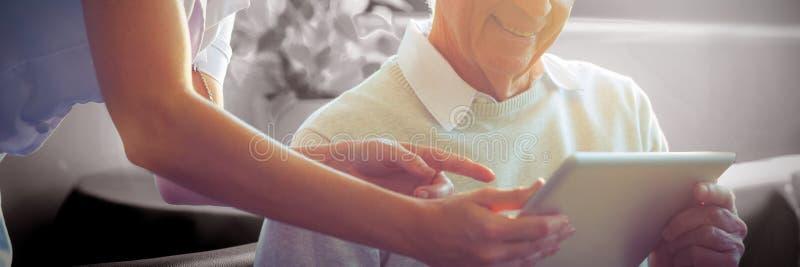 Weibliche Krankenschwester, die dem älteren Mann ärztlichen Attest über digitale Tablette zeigt stockfoto