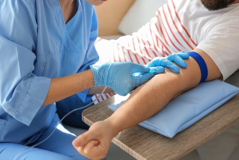 Weibliche Krankenschwester, die männlichen Spender für Bluttransfusion im Krankenhaus vorbereitet lizenzfreie stockfotografie