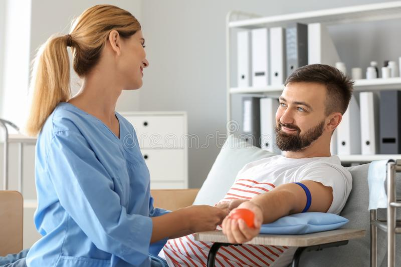 Weibliche Krankenschwester, die männlichen Spender für Bluttransfusion im Krankenhaus vorbereitet lizenzfreies stockfoto