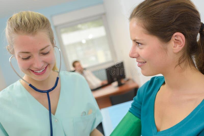 Weibliche Krankenschwester, die zu Hause ältere Frau des Blutdruckes überprüft stockfotografie