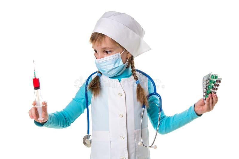 Weibliche Krankenschwester, welche die medizinische Maske hält die Spritze und die Pillen in den Händen, die Spritze in der recht lizenzfreie stockbilder