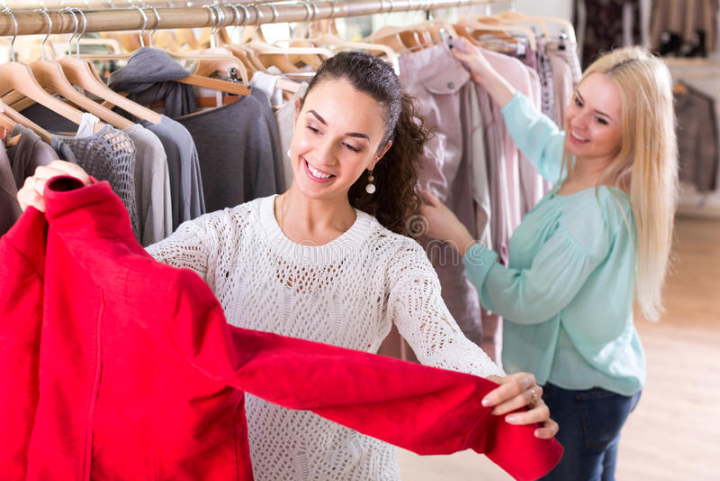Weibliche Kunden, die Mäntel und Jacken vorwählen lizenzfreie stockfotografie