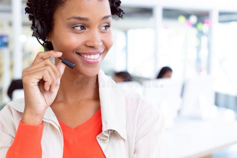Weibliche Kundendienstexekutivstellung mit Kopfhörerstellung im Büro stockbild
