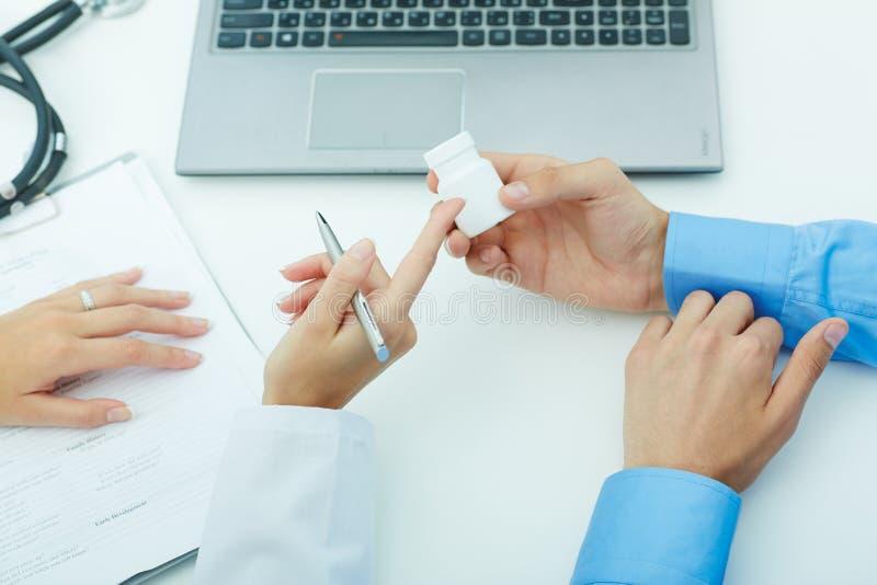 Weibliche Medizindoktorhände halten Glas Pillen Doktor erklärt den Patienten, wie man tägliche Dosis von Pillen benutzt stockfoto