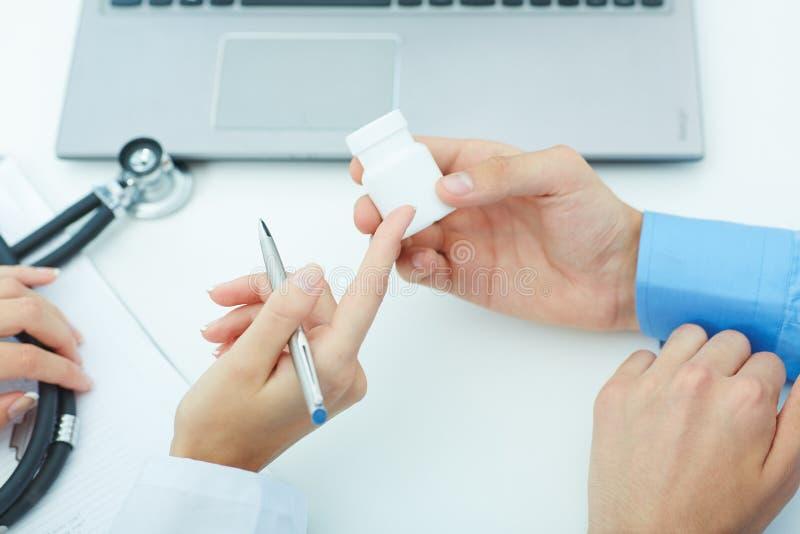 Weibliche Medizindoktorhände halten Glas Pillen und erklären den Patienten, wie man tägliche Dosis von Pillen benutzt lizenzfreies stockfoto