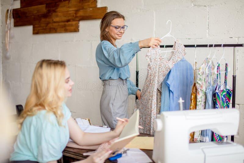 Weibliche Näherin, die Eigenschaften des Auftrages mit Kunden im gemütlichen Studio bespricht stockfotografie