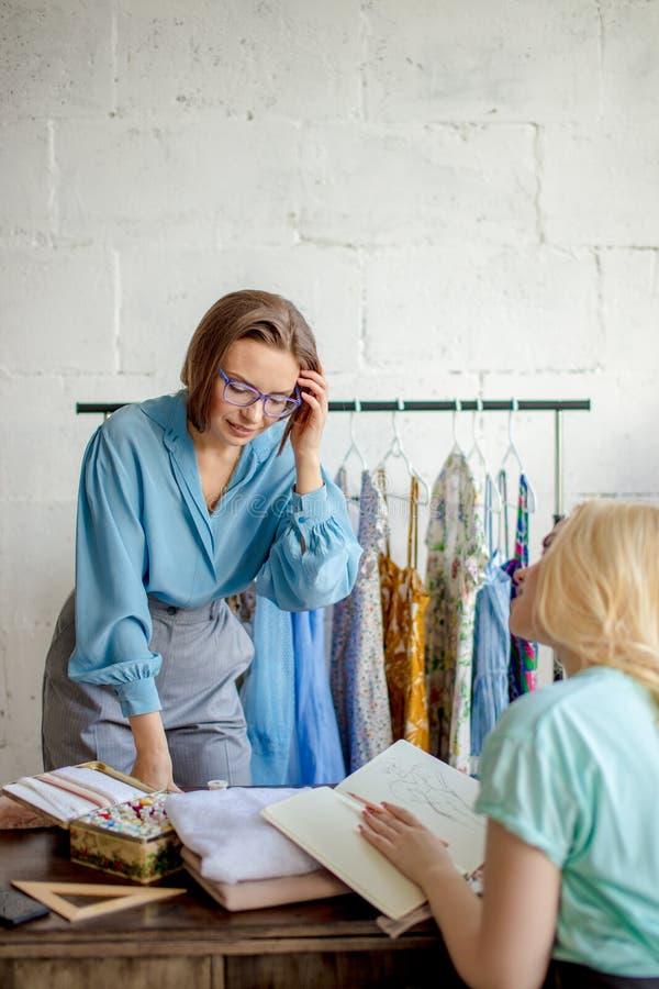 Weibliche Näherin, die Eigenschaften des Auftrages mit Kunden im gemütlichen Studio bespricht lizenzfreie stockfotos