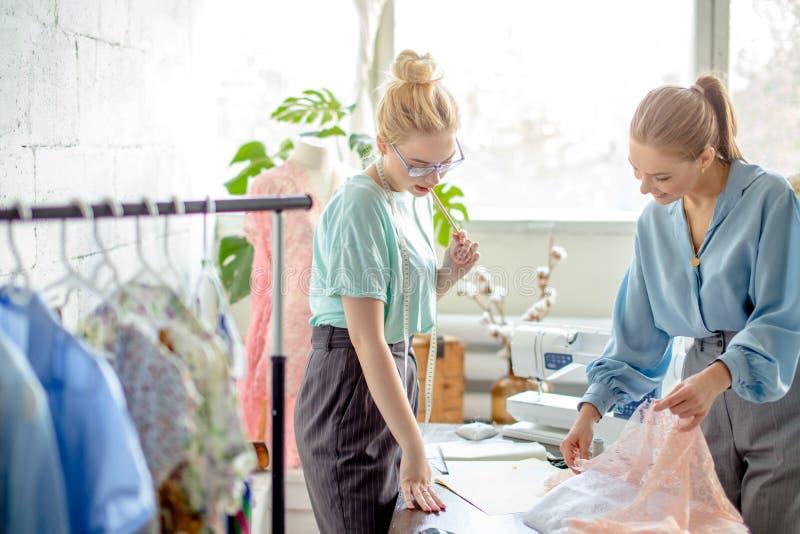 Weibliche Näherin, die Eigenschaften des Auftrages mit Kunden im gemütlichen Studio bespricht lizenzfreies stockbild