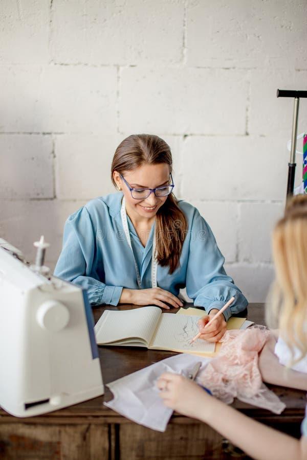 Weibliche Näherin, die Eigenschaften des Auftrages mit Kunden im gemütlichen Studio bespricht stockfotos