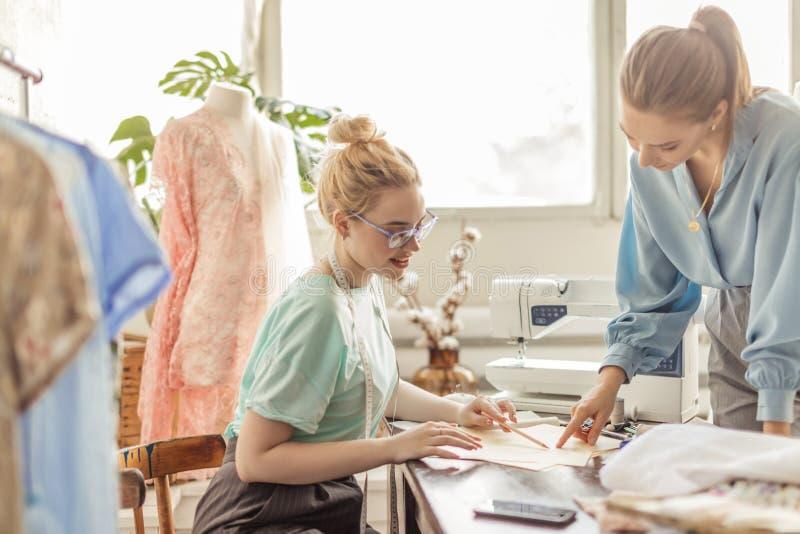 Weibliche Näherin, die Eigenschaften des Auftrages mit Kunden im gemütlichen Studio bespricht stockfoto
