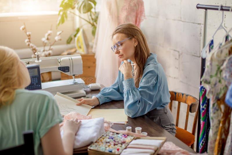 Weibliche Näherin, die Eigenschaften des Auftrages mit Kunden im gemütlichen Studio bespricht stockbilder