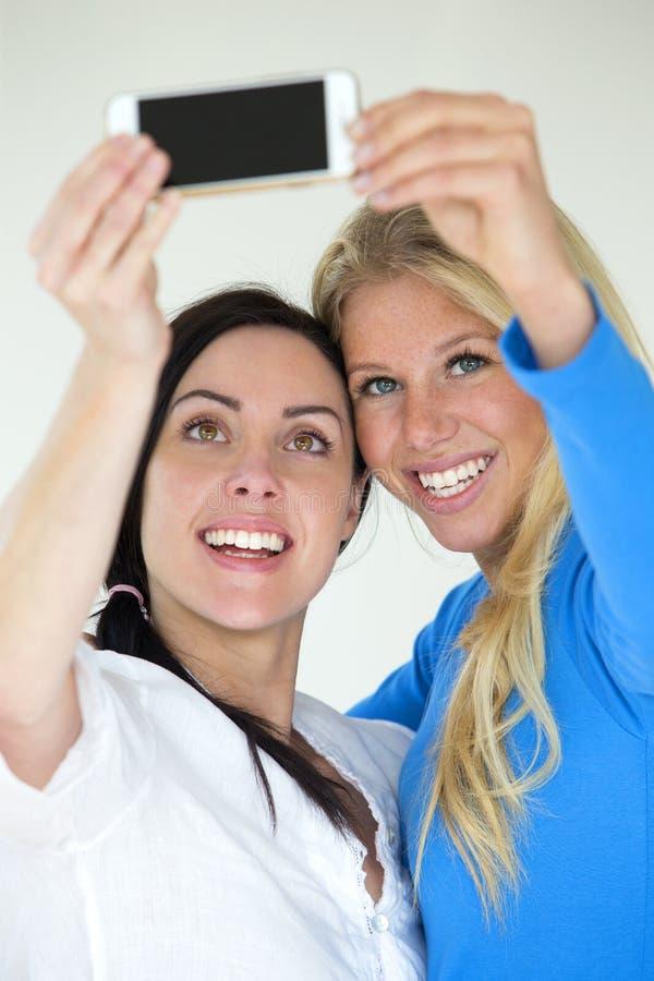 Weibliche Paare, die ein selfie nehmen lizenzfreies stockbild