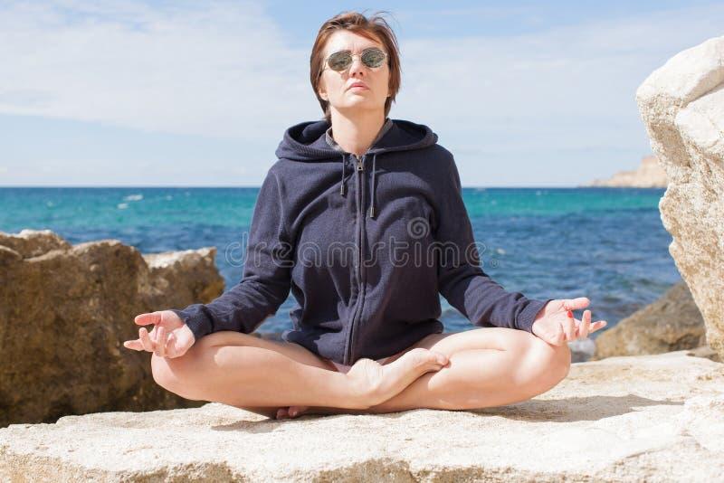 Weibliche Person, die auf wilder felsiger Küste sich entspannt lizenzfreie stockbilder