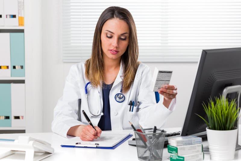 Weibliche pharmacis, die in der Hand Anmerkungen mit Kästen Medizin schreiben stockbild