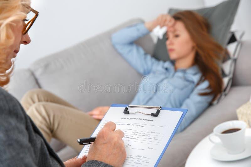 Weibliche psychologyst Therapie-Sitzung mit dem Kunden, der auf dem Sofa zuhause erfüllt Form liegt lizenzfreie stockbilder