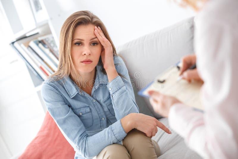 Weibliche psychologyst Therapie-Sitzung mit dem Kunden, der zuhause das Mädchen durchdacht sitzt stockfoto