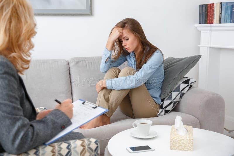 Weibliche psychologyst Therapie-Sitzung mit dem Kunden, der zuhause das Mädchen schaut hinunter deprimiertes sitzt stockfoto