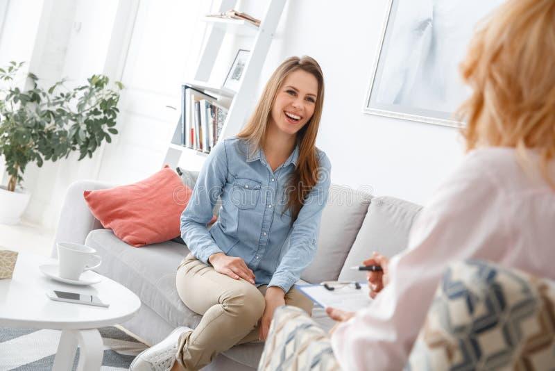 Weibliche psychologyst Therapie-Sitzung mit dem Kunden, der zuhause das Mädchenlächeln nett sitzt stockfotografie