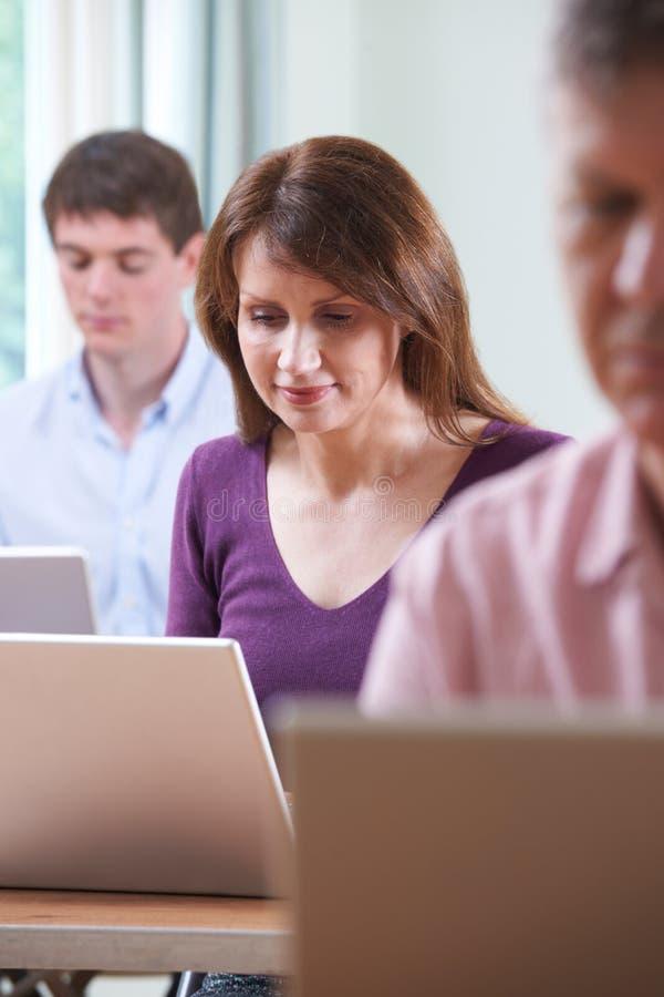 Weibliche reife Studenten-In Adult Educations-Computer-Klasse lizenzfreie stockfotos