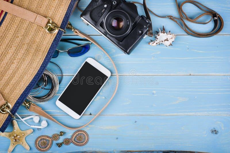 Weibliche Sachen der Sommerreise über tropischem blauem strukturiertem hölzernem Hintergrund stockfotografie