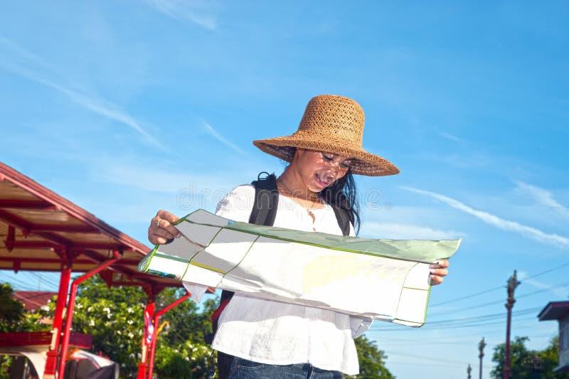 Weibliche schauende Karte des recht asiatischen Reisendwanderers am Bahnhof stockfotos