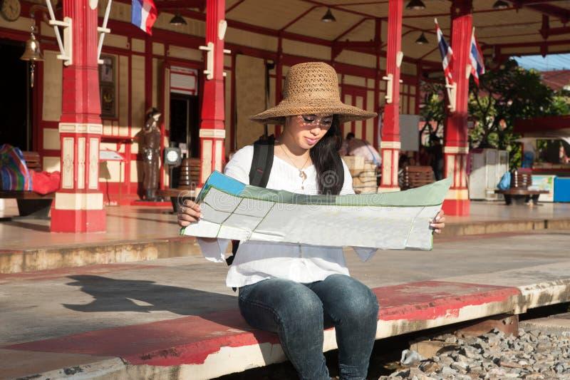 Weibliche schauende Karte des recht asiatischen Reisendwanderers am Bahnhof stockbilder